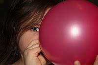 Niña infando un globo, kid blowing,niña globo