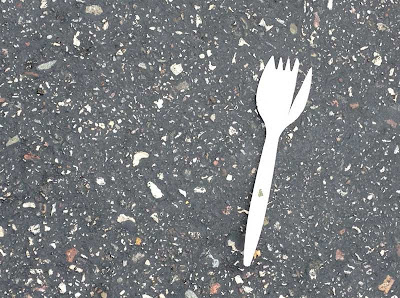 White plastic spork on asphalt