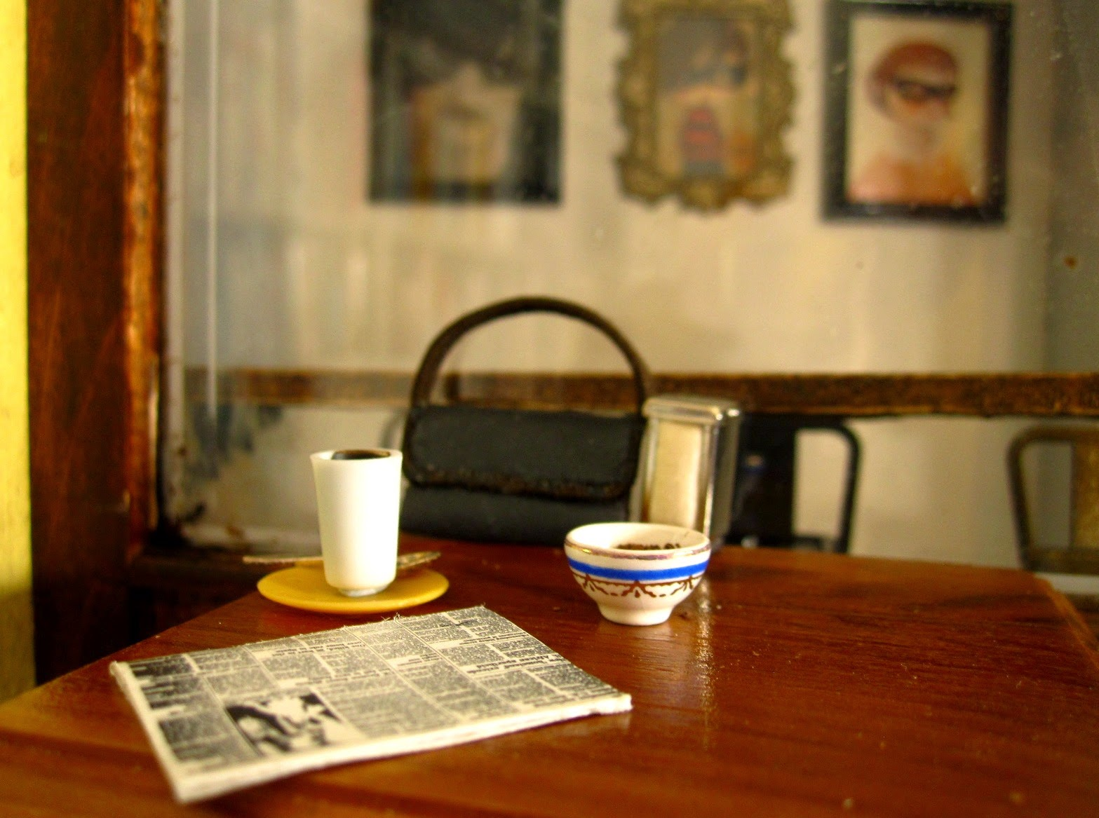 Modern dolls' house miniature cafe table with a newspaper, a latte, a sugar bowl and a handbag on it.