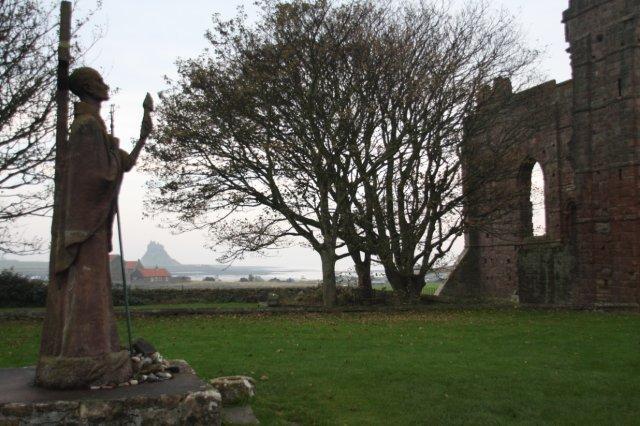La Isla Sagrada de Lindisfarne The Holy Island of Lindisfarne – Monasterio de Lindisfarne y Estatua de San Aidan. Al fondo, Castillo de Lindisfarne
