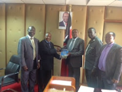 The Principal Secretary Industry Dr. Wilson Songa receives the SME Handbook from Mr. Muteti