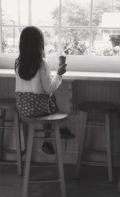 girl at a counter looking out a window and eating an ice cream cone