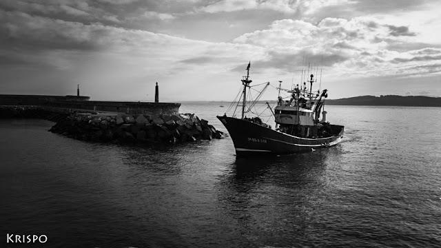 foto en blanco y negro de barco pesquero entrando a puerto en Hondarribia