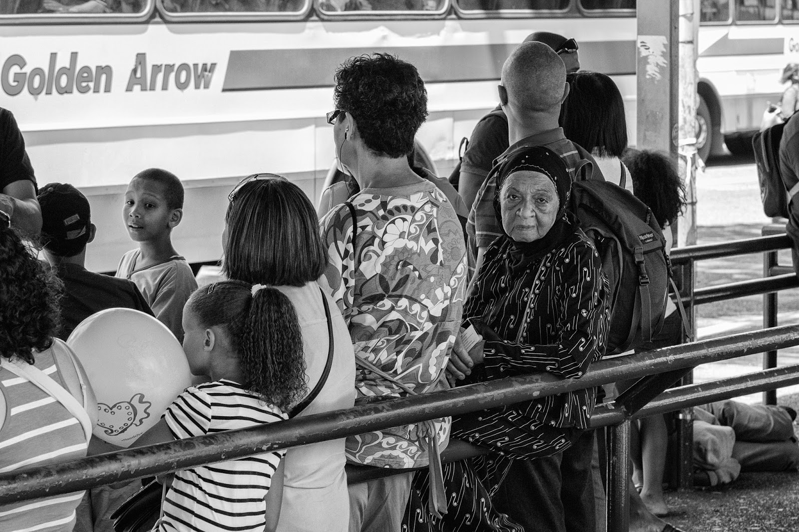 A woman looks back from the bus queue - the only other face visible is a young boy.