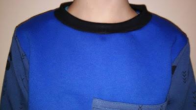 Bluza chłopięca w rozmiarze 128 z niebieskiej dresówki lekko drapanej i dodatkami dresówki pętelki w pandy.