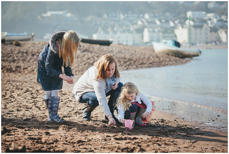 Mother playing with daughters on the beach