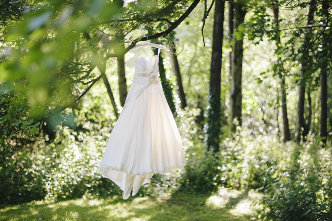 Gorgeous wedding dress hanging from a tree photo by STUDIO 1208