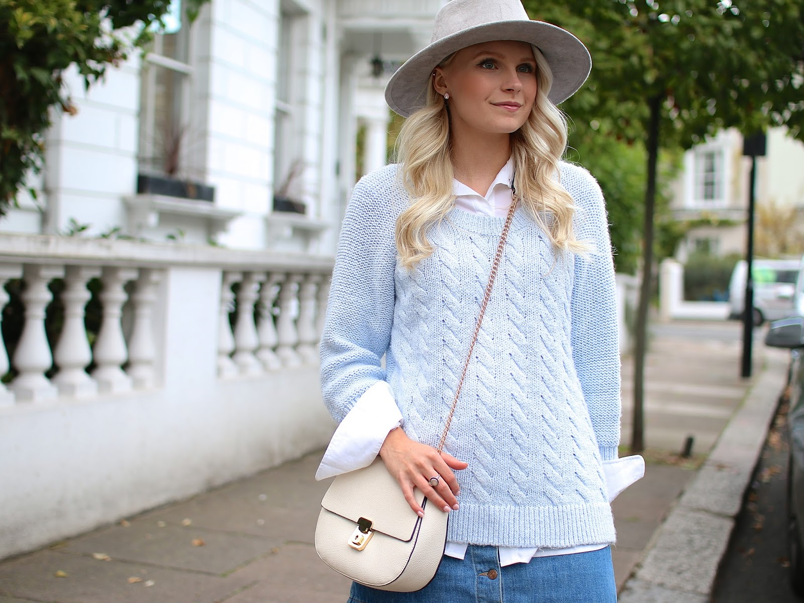 a blonde women wearing a cozy pale blue sweater in soho london