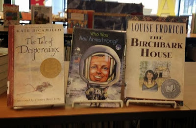 "From left to right, books in display stands: ""The Tale of Despereaux"" by Kate DiCamillo, ""Who was Neil Armstrong?"" by Roberta Edwards and ""Birchbark House"" by Louise Erdrich"