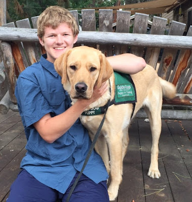 Sam sits on a wooden deck smiling with his arms around a yellow Lab guide dog puppy