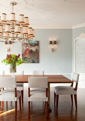 Dining room with moulded ceiling, a large chandelier, a long wood table surrounded by chairs white white cushions and a wood floor