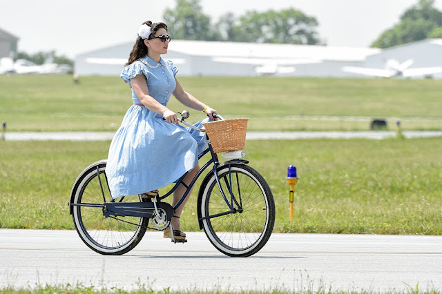 A girl in WWII period clothing riding a bike