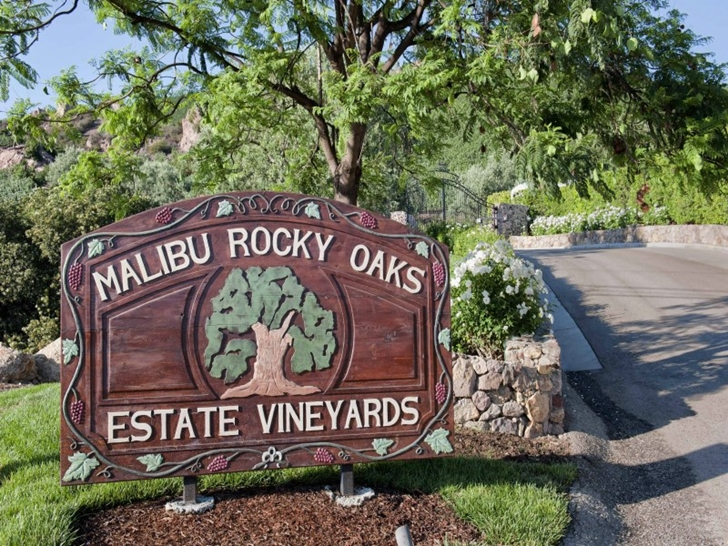 Wooden sign in front of Mediterranean style vineyards home in Malibu