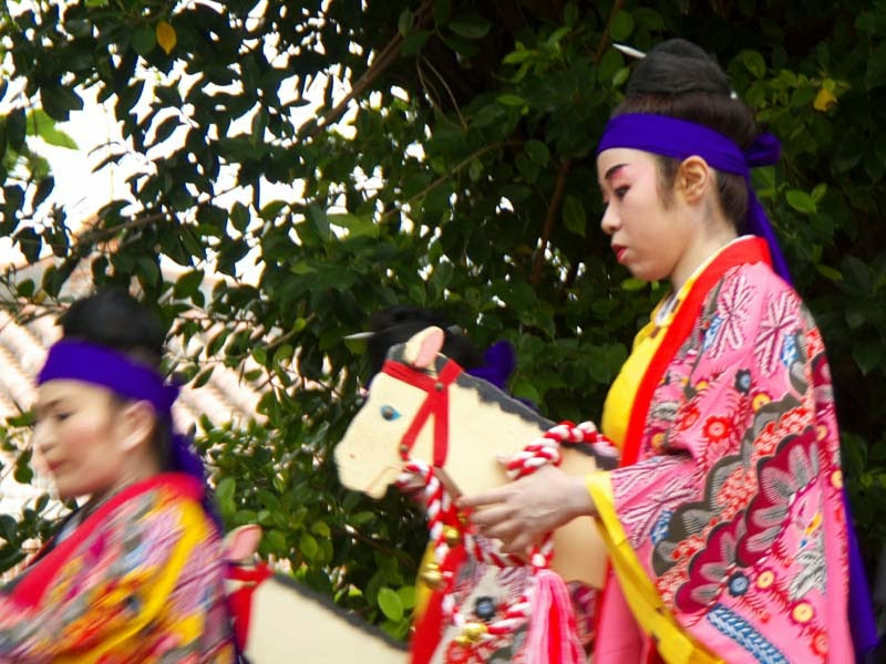 Kimono clad women dance riding wooden horses