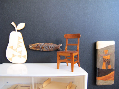 Modern dolls' house miniature display wall in a gallery. On display are a wooden pear, fish and chair, and wall plaque.