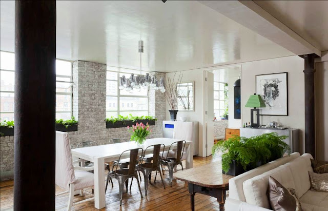 open plan living room dining room with white washed exposed brick walls, long white dining table and the French metal cafe chairs