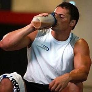 Культурист пьет белковый коктейль. Фото