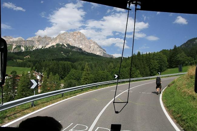 Imagem através do vidro da frente de um autocarro, mostrando um caminheiro a subir a montanha pela beira da estrada