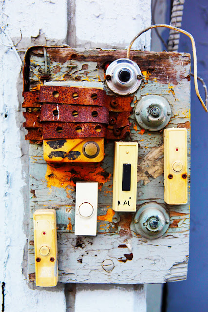 Eight dated doorbells outside an apartment building in New York City.