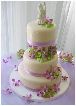 cake decorated with purple orchids green leaves and lavender satin