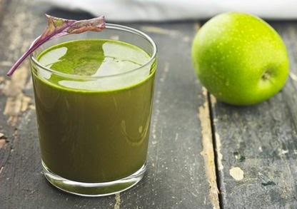 A green juice in a glass next to a green apple