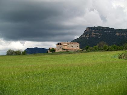 El Mas de L'Espunyola amb el Serrat de Malla a la dreta i el Cap dels Plans a l'esquerra