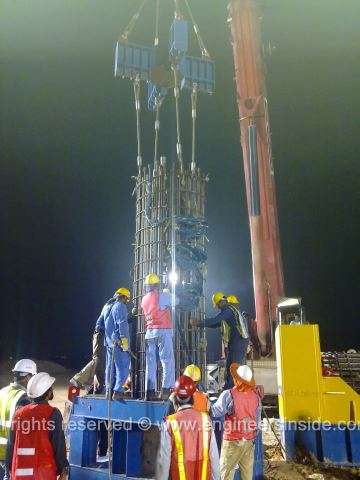 Workers working on lowering the test pile