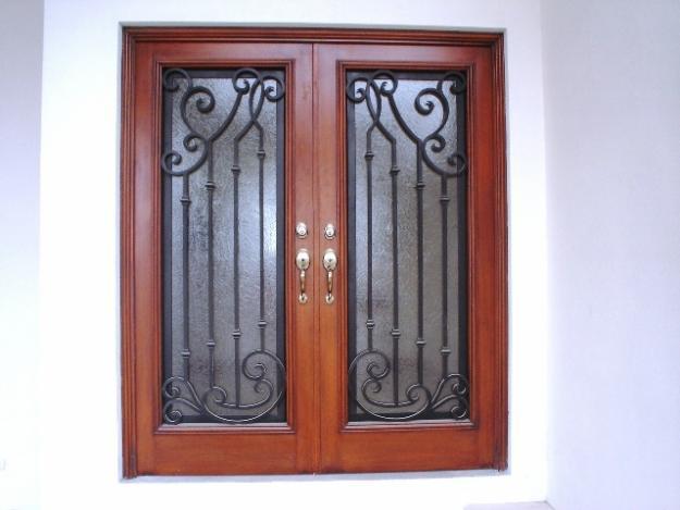 Herreria machuca puerta tipo forja en acabado madera for Puertas de madera con herreria