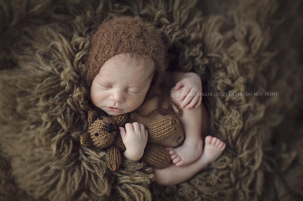 newborn cuddling teddy bear