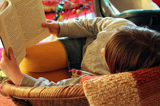 Photo shows a girl reading in a chair. Photo is taken from behind her. She wears yellow tights, a mini skirt, a gray sweater, and her hair is parted down the middle. A toy is in the far background. She is about 12 years old.
