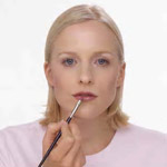 a woman applying lip gloss