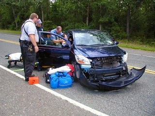 Car accident victim helped by those who specialize in rendering first aid.