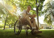 Young light-skinned thin man in a manual wheelchair on an expanse of green lawn with the sun shining through several trees around him. His hands are clasped, with elebows on knees, and he's leaning forward and smiling.