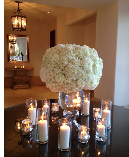 Romantic and ruffled white floral arrangement with candles