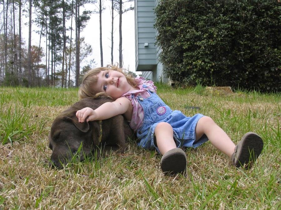 صورة لطفلة نائمة على كلبها