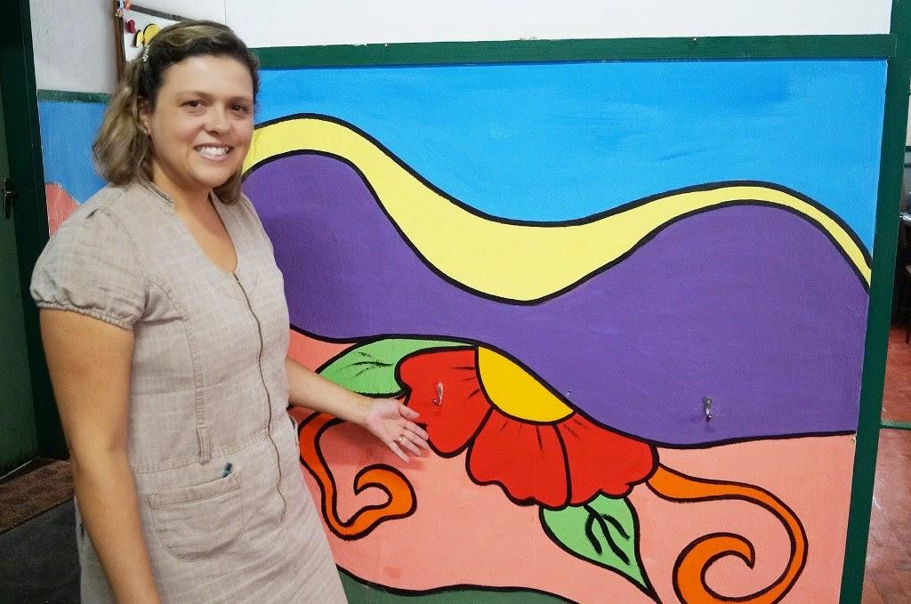 A nova diretora, Alessandra Rezende mostra parte da colorida pintura realizada na Escola Municipal Hilário Ribeiro