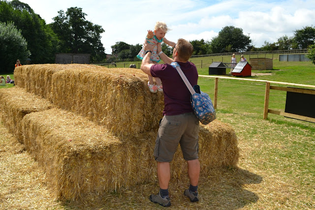 Mr Tin Box catching Tin Box Tot as she jumps off the top of a pile of hay bales