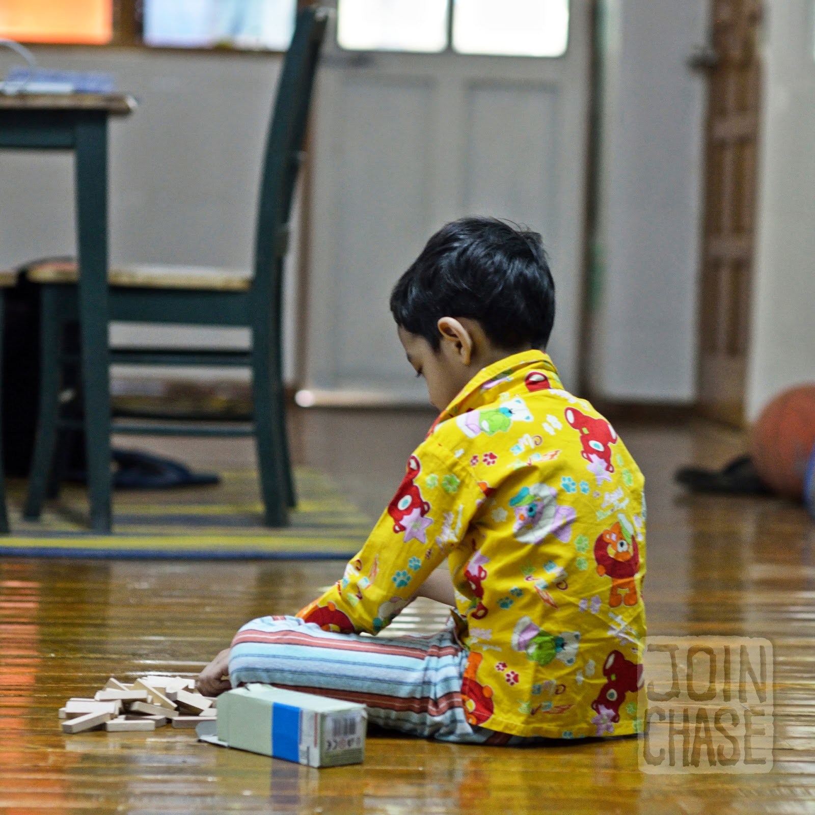 A boy playing with blocks on the floor of an apartment in Yangon, Myanmar.