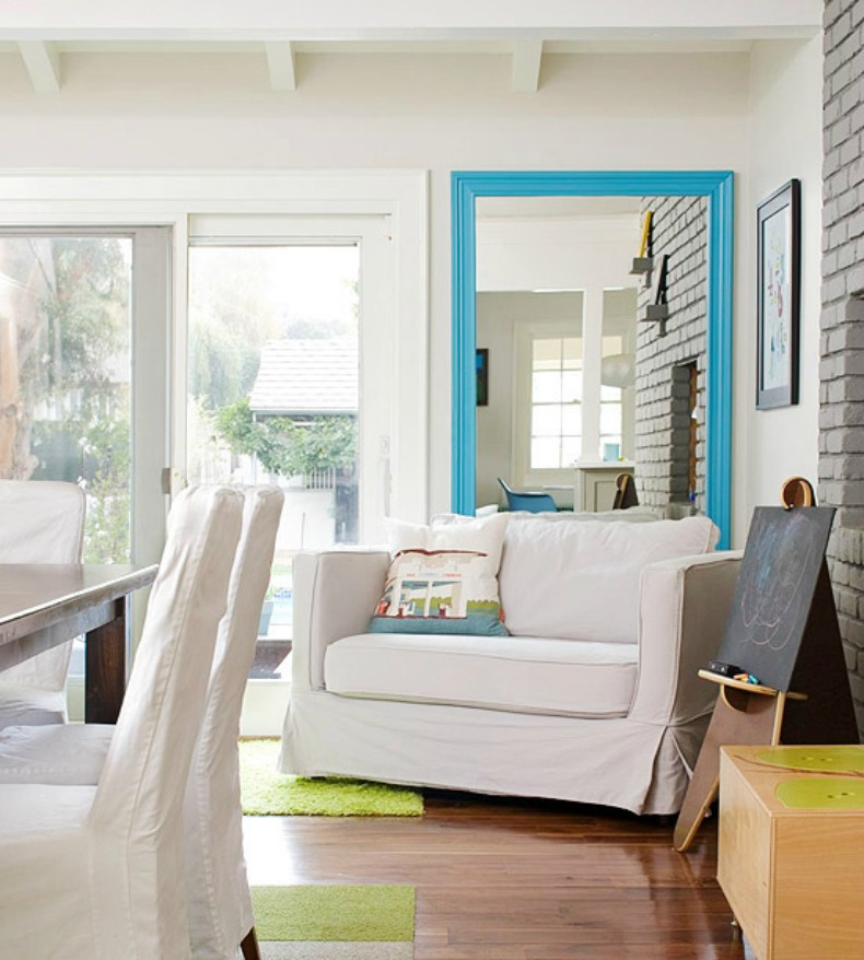 Coastal dining room with white slipcover chairs and large aqua mirror