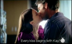 kay jewelers ad that says &quot;Every kiss begins with Kay&quot; over couple kissing