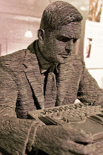 That's Alan Turing, or rather, a staute of him.