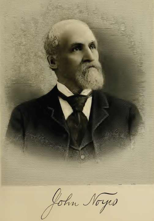 John Noyes, balding with long white beard. He's dressed in suit and tie fitting his wealthy status in 1901.