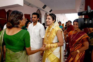 The bride shine in gold jewels as she interact with her mother in law.