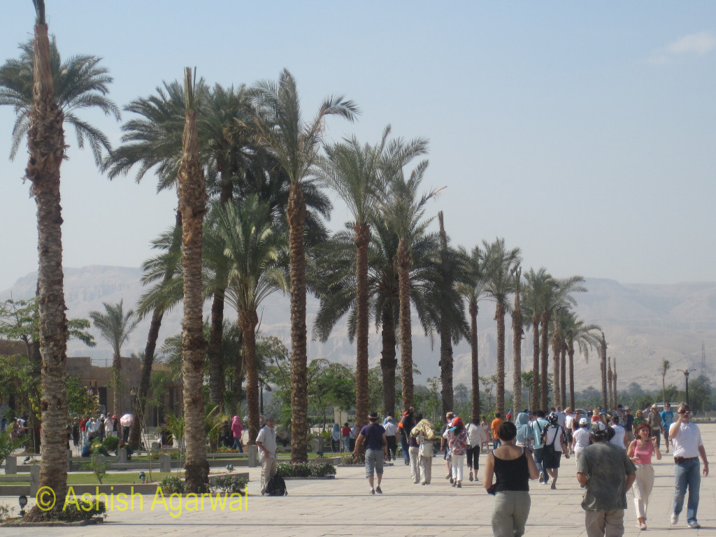 Tourists walking away from the Karnak temple in Luxor, with hills in front