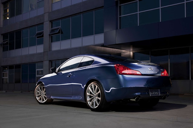 Rear 3/4 view of blue 2011 Infiniti G37 Coupe parked in front of office building at night