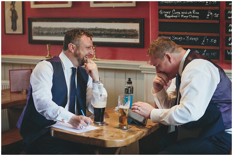 Groom and best man writing their speeches in the pub on the wedding day