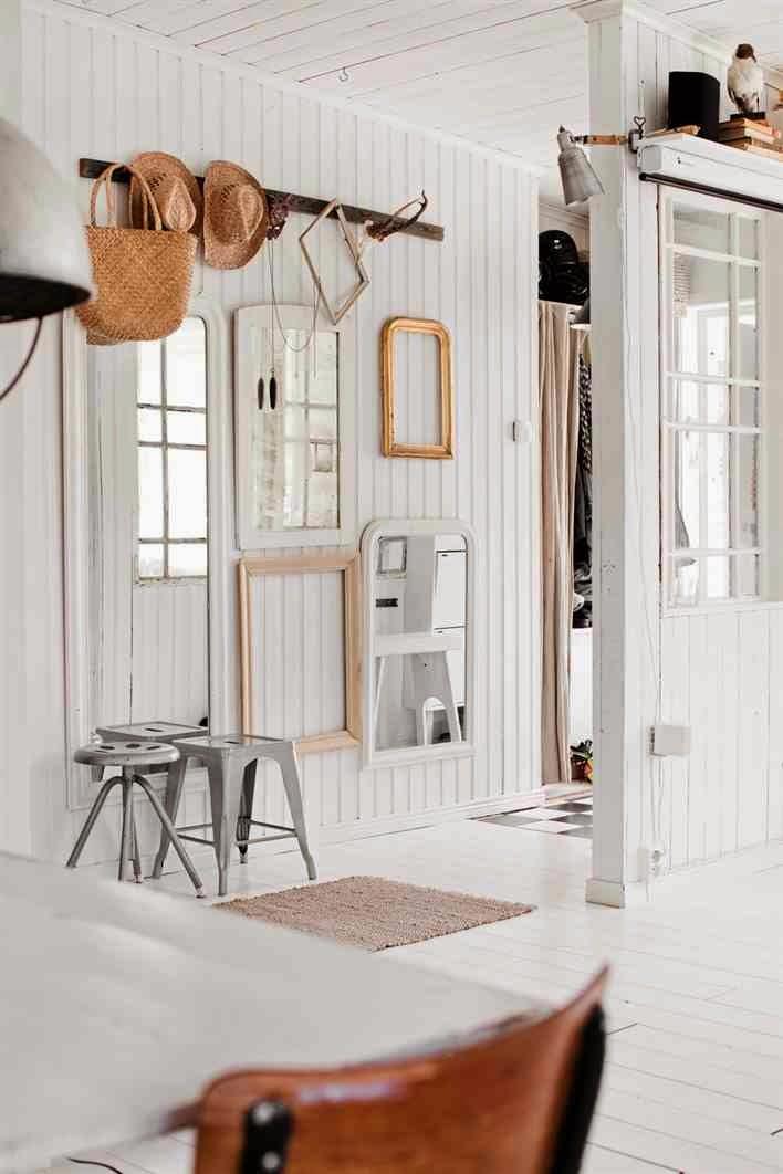 Industrialny metalowy taboret, ściana z białych desek, eklektyczny przedpokój, puste ramy na ścianach