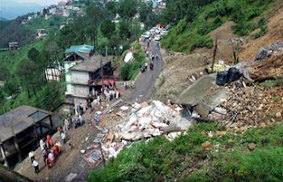 People looking at the rubbles of the two houses that collapsed due to heavy rains in Shimla on Monda