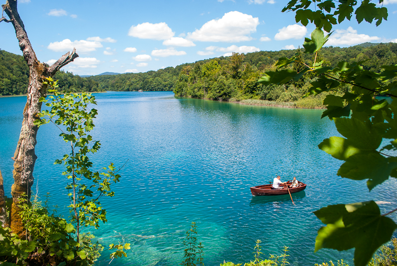 stunning view of the Plitvice Lakes National Park and people rowing boats on the lake