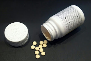 medicine bottle open with pills spilling out